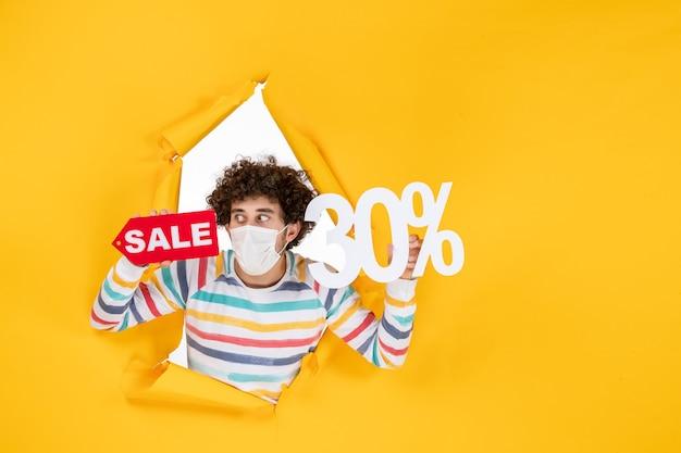 Widok z przodu młody mężczyzna w masce trzymający żółty kolor pandemiczny zakupy czerwony zdrowie covid photo wirus wyprzedaż