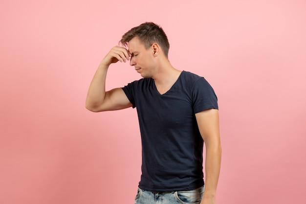 Widok z przodu młody mężczyzna w niebieskiej koszulce cierpi na bóle głowy na różowym tle model koloru męskiej emocji człowieka