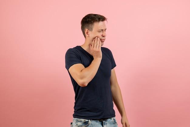 Widok z przodu młody mężczyzna w niebieskiej koszulce o bólu zęba na różowym tle mężczyzna emocja kolor modelu człowieka