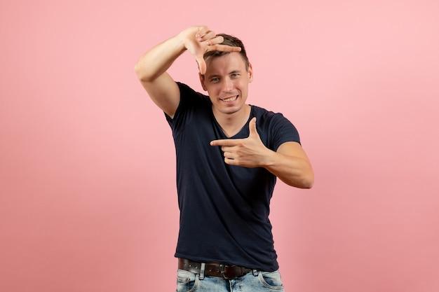 Widok z przodu młody mężczyzna w niebieskiej koszulce przedstawiający znak z obrazkiem na różowym tle męski model kolorów emocji człowieka