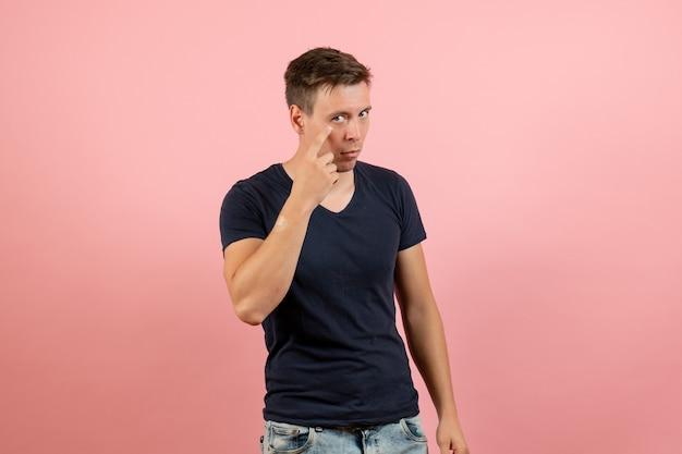 Widok z przodu młody mężczyzna w niebieskiej koszulce stwarzających na różowym tle mężczyzna emocja kolor modelu człowieka