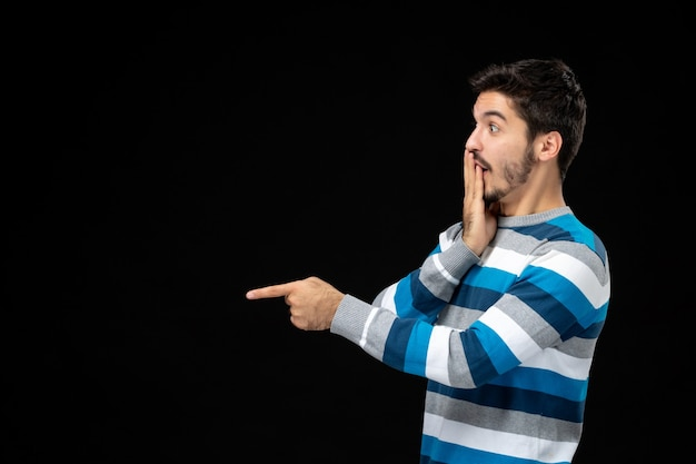 Widok z przodu młody mężczyzna w niebieskiej koszulce w paski na czarnej ścianie model zdjęcia w kolorze ciemności