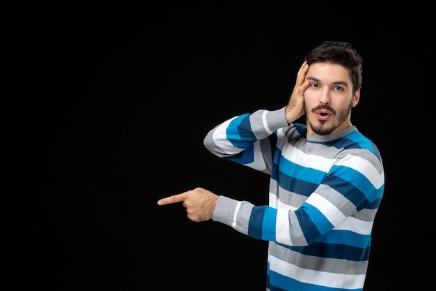 Widok z przodu młody mężczyzna w niebieskiej koszulce w paski na czarnej ścianie