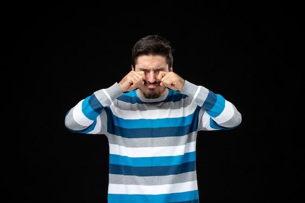 Widok z przodu młody mężczyzna w niebieskiej koszulce w paski płacze