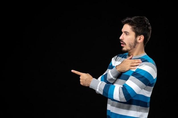 Widok z przodu młody mężczyzna w niebieskiej koszulce w paski, wskazując na miejsce na kopię