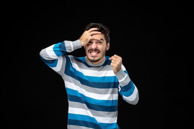 Widok z przodu młody mężczyzna w niebieskiej koszulce w paski z sfrustrowanym wyrazem twarzy