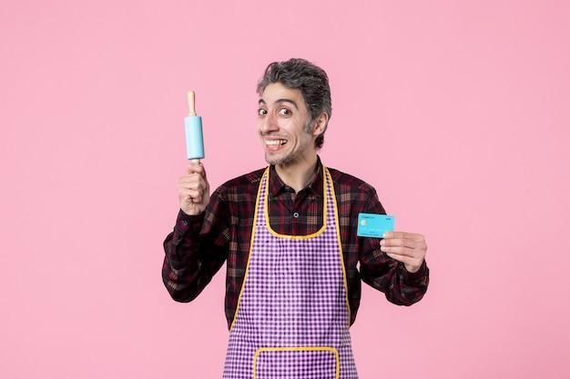 Widok z przodu młody mężczyzna w pelerynie trzymający mały wałek do ciasta i kartę bankową na różowym tle pieniądze zawód mąż poziome gotowanie praca pracownik kuchnia