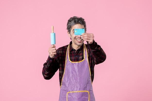 Widok z przodu młody mężczyzna w pelerynie trzymający wałek do ciasta i kartę bankową na różowym tle zawód mąż poziomy mundur kuchenny gotowanie robotnik
