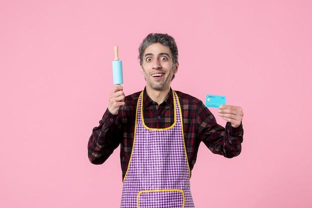 Widok z przodu młody mężczyzna w pelerynie trzymający wałek do ciasta i kartę bankową na różowym tle zawód mąż pracownik mundur kuchenny pieniądze praca w kuchni
