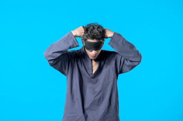 Widok z przodu młody mężczyzna w piżamie i śpiącym bandażu na niebieskim tle noc kolor koszmar sypialnia ciemne łóżko sen sen odpoczynek