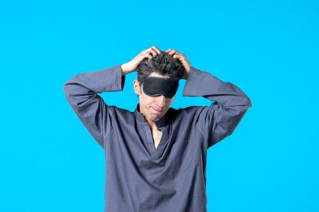 Widok z przodu młody mężczyzna w piżamie i śpiącym bandażu na niebieskim tle odpoczynek ciemna sypialnia koszmar noc kolor łóżko sen