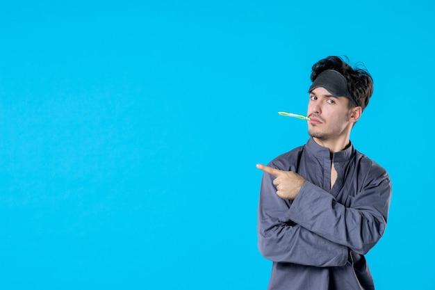 Widok z przodu młody mężczyzna w piżamie ze szczoteczką do zębów w ustach na niebieskim tle kolor nocy sen poduszka koszmar budzenie odpoczynek łóżko ciemno