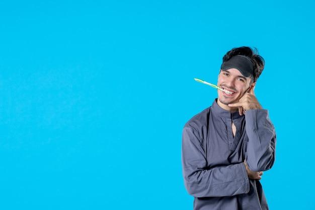 Widok z przodu młody mężczyzna w piżamie ze szczoteczką do zębów w ustach na niebieskim tle noc kolor poduszka koszmar przebudzenie odpoczynek ludzkie łóżko ciemno