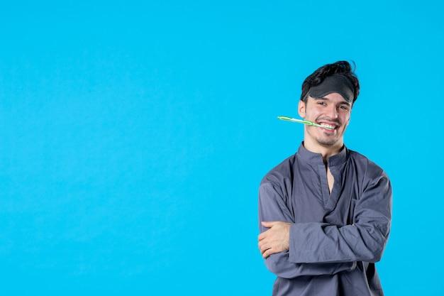 Widok z przodu młody mężczyzna w piżamie ze szczoteczką do zębów w ustach na niebieskim tle noc kolor sen poduszka obudź odpoczynek ludzkie łóżko ciemno