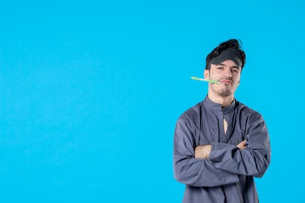 Widok z przodu młody mężczyzna w piżamie ze szczoteczką do zębów w ustach na niebieskim tle odpoczynek noc kolor obudź sen koszmar ludzkie łóżko ciemno