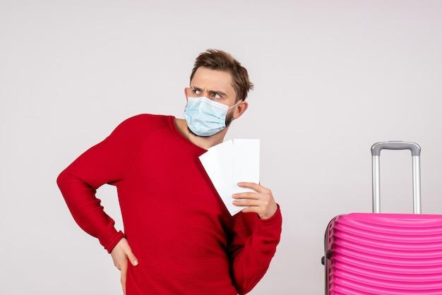 Widok z przodu młody mężczyzna w sterylnej masce trzymający bilety na białej ścianie covid- samolot wakacje emocje wirusa lot kolor podróż