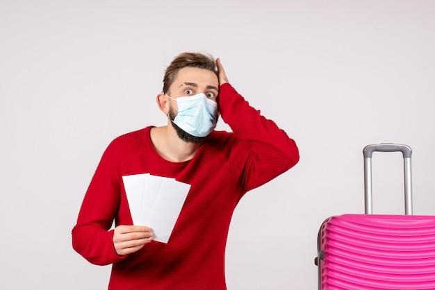 Widok z przodu młody mężczyzna w sterylnej masce trzymający bilety na białej ścianie podróż covid - kolor lotu wirusa emocji podróży