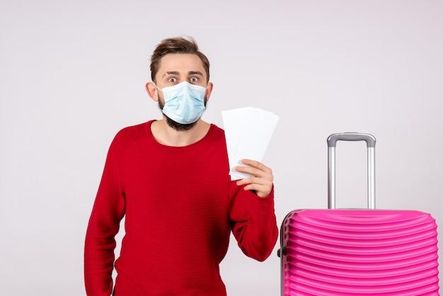 Widok z przodu młody mężczyzna w sterylnej masce trzymający bilety na białej ścianie podróż covid - podróż wakacje kolor emocji lot wirusa