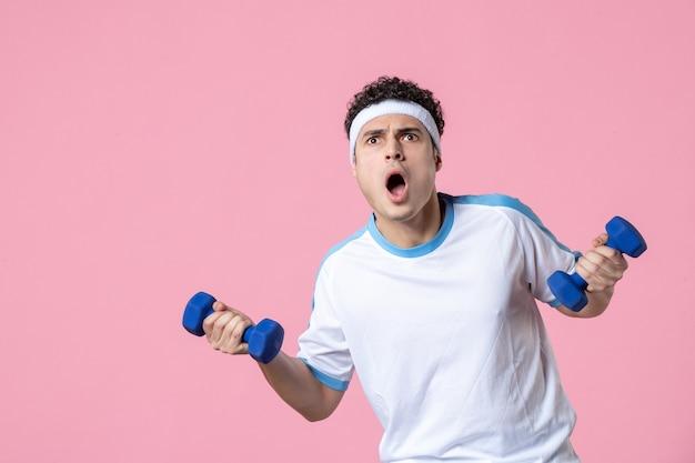 Widok z przodu młody mężczyzna w strojach sportowych z hantlami na różowej ścianie