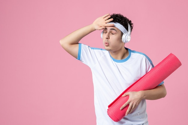 Widok z przodu młody mężczyzna w strojach sportowych z matą do jogi na różowej ścianie