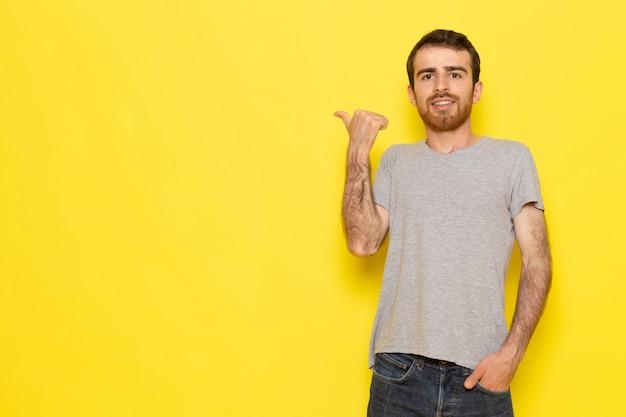 Widok z przodu młody mężczyzna w szarej koszulce na żółtej ścianie mężczyzna w kolorze ubrania modelu emocji