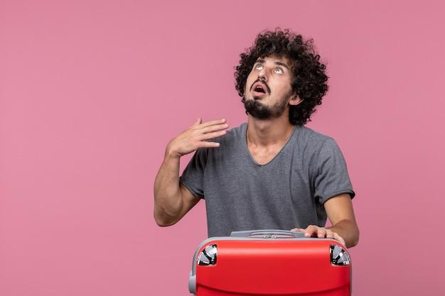 Widok z przodu młody mężczyzna w szarej koszulce przygotowuje się do podróży na różowej przestrzeni