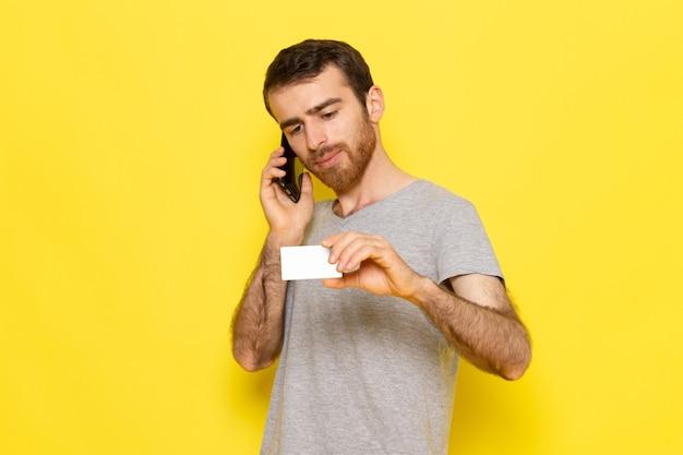 Widok z przodu młody mężczyzna w szarej koszulce trzyma białą kartę i rozmawia przez telefon na żółtej ścianie model koloru wyrażenie emocji człowieka
