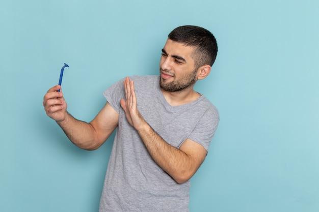 Widok z przodu młody mężczyzna w szarej koszulce trzymając brzytwę na niebieskiej brodzie do golenia męskiej pianki do włosów