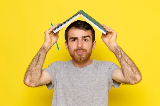 Widok z przodu młody mężczyzna w szarej koszulce trzymając zeszyt na żółtej ścianie mężczyzna kolor model emocji ubrania