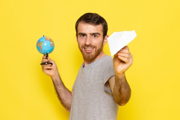 Widok z przodu młody mężczyzna w szarej koszulce trzymającej małą kulę ziemską i papierowy samolot na modelu koloru żółtego człowieka na biurku
