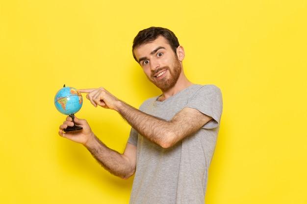 Widok z przodu młody mężczyzna w szarej koszulce trzymającej małą kulę ziemską z uśmiechem na żółtej ścianie mężczyzna kolor ubrania modelu emocji