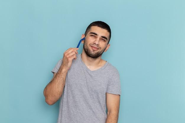 Widok z przodu młody mężczyzna w szarej koszulce trzymający brzytwę i golący twarz na niebieskiej brodzie do golenia męski kolor pianki do włosów