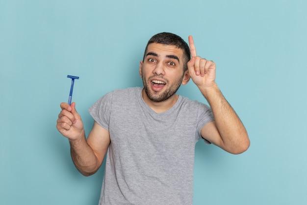 Widok z przodu młody mężczyzna w szarej koszulce trzymający brzytwę na niebieskim goleniu brody w kolorze pianki do włosów