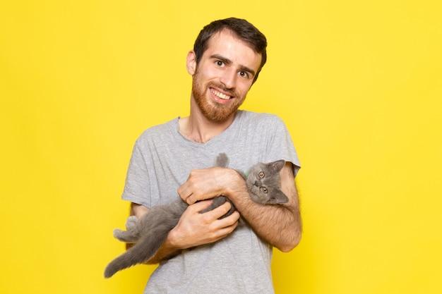 Widok z przodu młody mężczyzna w szarej koszulce trzymający szarego kota z uśmiechem na żółtej ścianie model wyrazu emocji człowieka