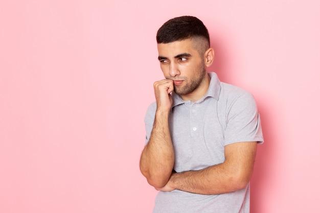 Widok z przodu młody mężczyzna w szarej koszuli myśli głęboko na różowo