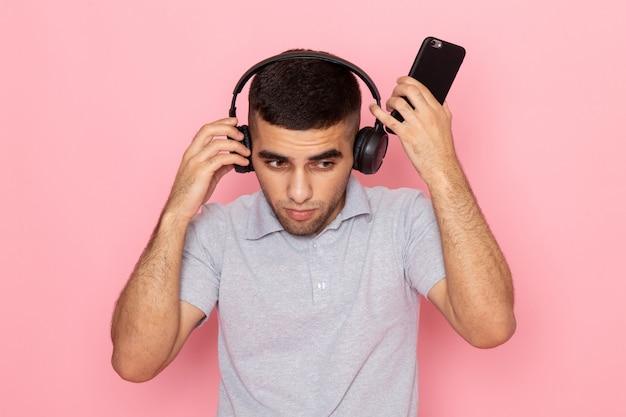 Widok z przodu młody mężczyzna w szarej koszuli, trzymając telefon i słuchając muzyki na różowo