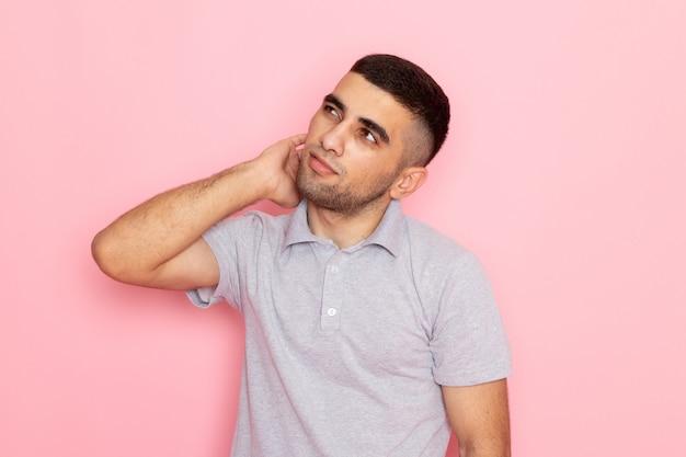 Widok z przodu młody mężczyzna w szarej koszuli z myślenia stanąć na różowo