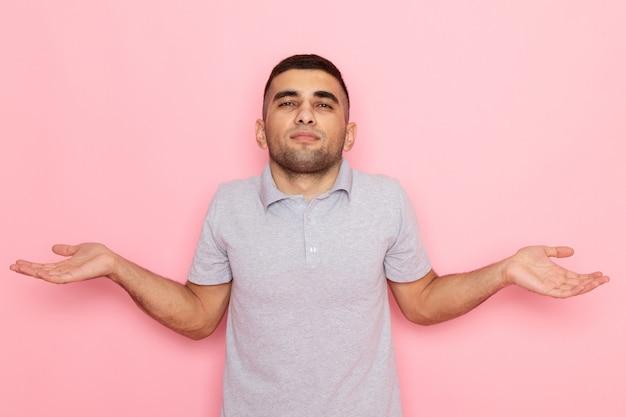 Widok z przodu młody mężczyzna w szarej koszuli z nieznanym wyrazem twarzy na różowo