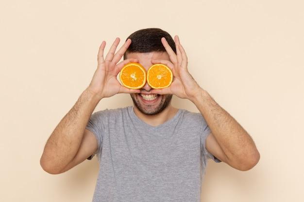 Widok z przodu młody mężczyzna w szarym t-shircie i niebieskich dżinsach, uśmiechnięty i trzymający pomarańczowe pierścienie na beżu