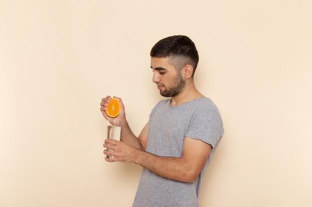 Widok z przodu młody mężczyzna w szarym t-shircie i niebieskich dżinsach wyciskający sok pomarańczowy na beż