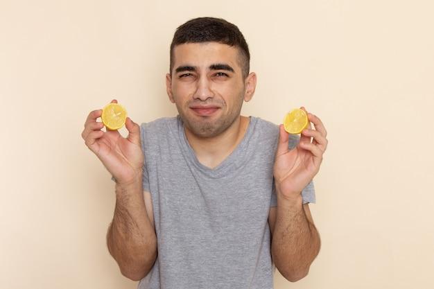 Widok z przodu młody mężczyzna w szarym t-shircie jedzący pierścienie z kwaśnej cytryny na beżu