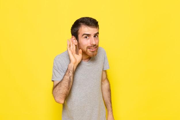 Widok z przodu młody mężczyzna w szarym t-shircie próbuje usłyszeć na żółtej ścianie mężczyzna kolor ubrania modelu emocji