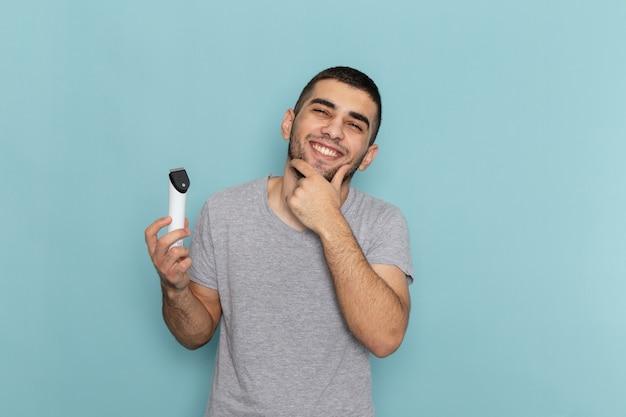 Widok z przodu młody mężczyzna w szarym t-shircie, trzymając elektryczną maszynkę do golenia, uśmiechając się na lodowobłękitnej męskiej piance do golenia brody
