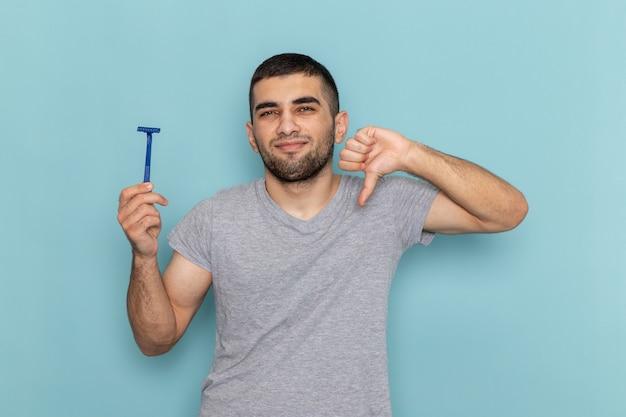 Widok z przodu młody mężczyzna w szarym t-shircie, trzymający brzytwę i pokazujący inny znak na niebiesko
