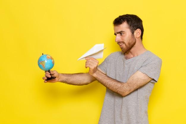 Widok z przodu młody mężczyzna w szarym t-shircie trzymający małą kulę ziemską i papierowy samolot na modelu koloru żółtej ściany