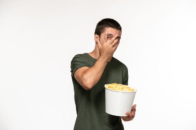 Widok z przodu młody mężczyzna w zielonej koszulce trzyma kipsy ziemniaczane oglądając film na białym biurku osoba samotna kino filmowe