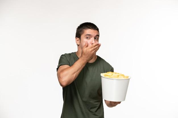 Widok z przodu młody mężczyzna w zielonej koszulce trzyma żetony ziemniaczane na białej ścianie film osoba w kinie