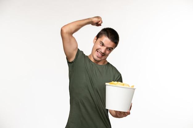 Widok z przodu młody mężczyzna w zielonej koszulce trzymając cips na białej ścianie osoba samotna kino filmowe
