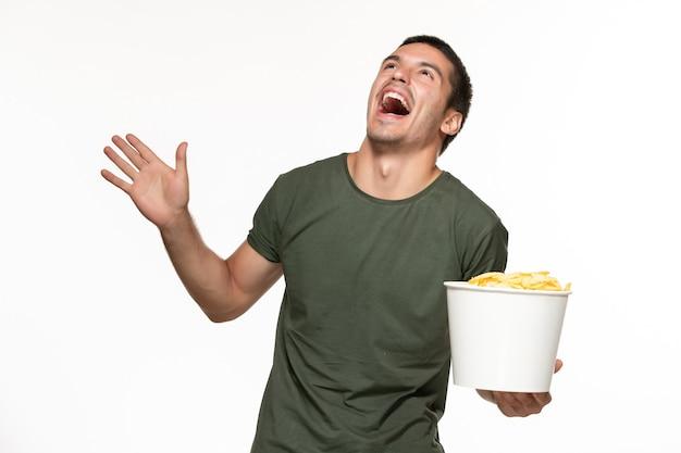 Widok z przodu młody mężczyzna w zielonej koszulce, trzymając kipsy ziemniaczane i oglądając film na białej ścianie samotne kino filmowe