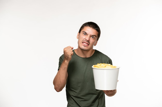 Widok z przodu młody mężczyzna w zielonej koszulce, trzymając kipsy ziemniaczane na jasnobiałej ścianie samotny film filmowy osoba w kinie